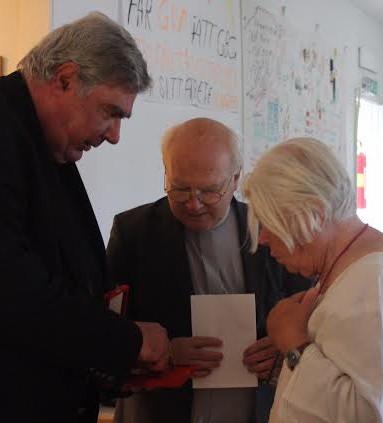 Gun får utmärkelsen av sändebudet Stefan Herczfeld och katolska prästen Daniel Pauchard. Foto: Raymond Ståhl