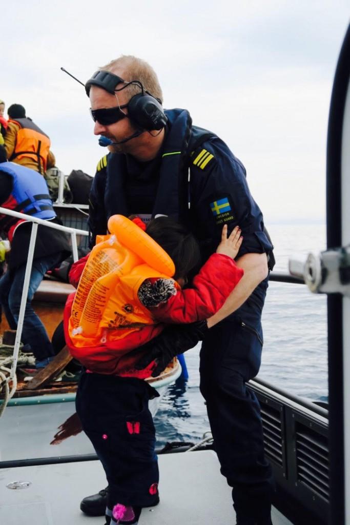 Jonas Grevstad hjälper ett barn iland, en av cirka 5 000 flyktingar som Kustbevakningen har räddat hittills. Foto: Kustbevakningen.
